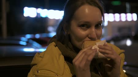 plavé vlasy : Happy smiling girl with a sparkles on her face eating hamburger on a night street. Handheld footage Dostupné videozáznamy