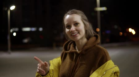 ярмарка : Young expansive woman sensually dancing outside in yellow jacket. Feel free, smiling. Handhelded footage