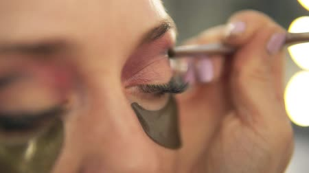 eyeshade : Make-up artist applying eye shadow to models eye. Close up view. Patches Stock Footage
