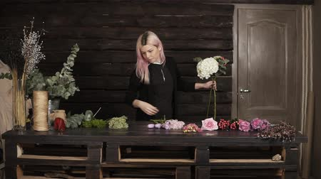 florista : Impressive front florist shooting at work. A nice girl collects flowers in a composition. Indoors
