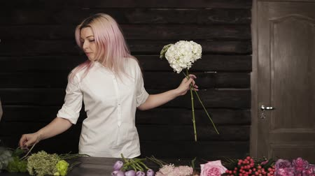 ortanca : Happy, beautiful girl florist in a white shirt enthusiastically chooses flowers for a composition from a wide assortment of flowers. Slow motion Stok Video