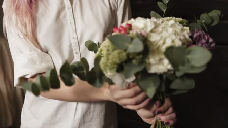 variedade : A beautiful bouquet design in the hands of a charming girl with pink hair and a white shirt. Slow motion