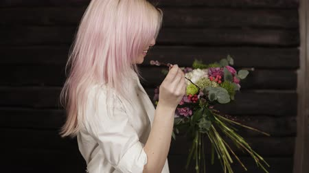 ortanca : A pink haired young woman makes the design of the bouquet, complementing the composition with willow branches. Smiling. Dark background Stok Video