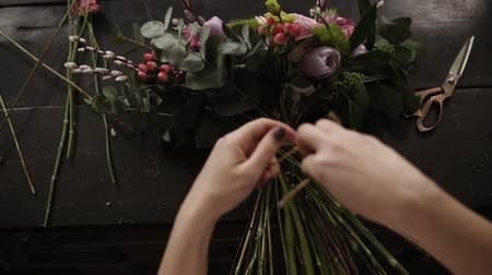 ortanca : A beautiful bouquet of flowers decorated by a florist lies on a table. The girl tightly tightens it with rope on the stems. View from above Stok Video