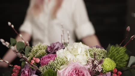 ortanca : Close-up of a colorful bouquet on the table changing to a footage of an attractive young smiling girl. Dark background. Slow motion Stok Video