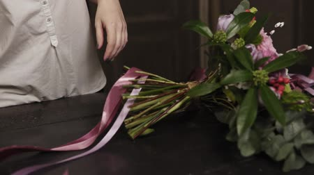tag : A girl in a white shirt cuts long pink ribbons and purple broad ribbons of guipure to decorate a bouquet of flowers on a table. Close up