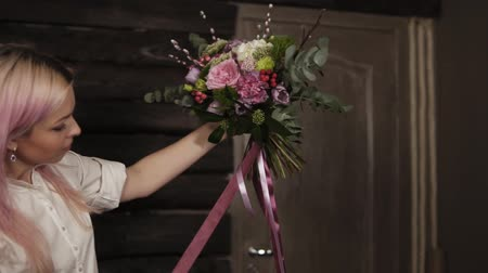 hortênsia : A girl with pink hair holds a variety of flowers in her hands in front of her. The bouquet is decorated with dangling silk ribbons. Side view