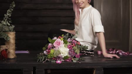 hortênsia : Beautiful slow motion footage of an amazing bouquet made by professional florist. Seductive, smiling girl in white shirt is sitting on the table. Studio Vídeos