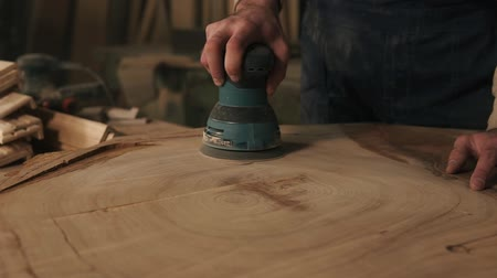 sander : Mens, rude, working hands of carpenter handle the wood with a grinding machine. Checks the smooth surface with the hand Stock Footage