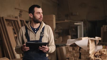 overall : A young man with a beard walks around the carpentry shop with a tablet in his hands. Looks back, evaluates