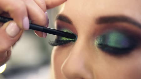gizemli : Extremely close applying shine bright green shadows on eye corner. Beautiful caucasian model