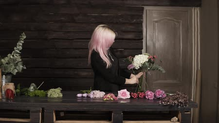szegfű : A pretty girl florist on a dark background makes a composition of flowers. Modern, wooden interior
