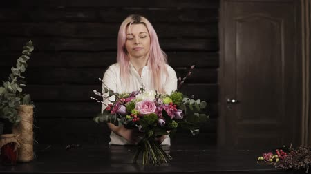 фиолетовый : A girl puts on a table a decorated bouquet of flowers. Surprised and laughs. Bouquet in the foreground. The dark interior. Slow motion Стоковые видеозаписи