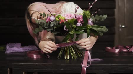szegfű : Professional girl florist binds the bottom of the bouquet with silk pink ribbons. Dark studio. Slow motion Stock mozgókép