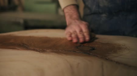 ポーランド語 : The carpenter with a rag in his hand processes the wood with oil after grindering. Close up 動画素材