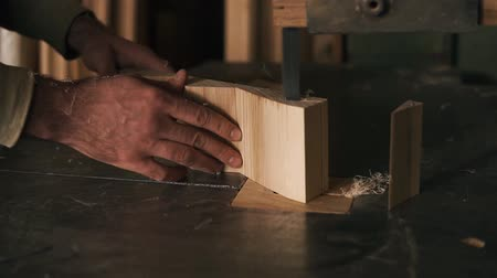 marangoz : With the help of electric saws, the masters hands cuts off excess parts from the bar, making shape. Sawdust fly from the machine. Close up