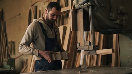 лесоматериалы : Carpenter shop. A nice worker cuts a ribbed shape from a wooden block using an electric saw machine. Evaluates the work, holding the product in hands Стоковые видеозаписи