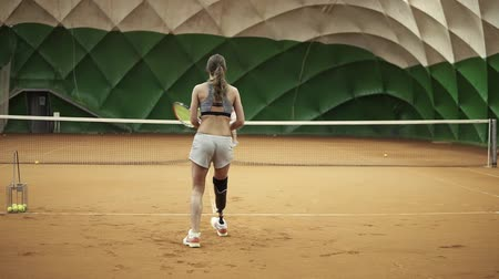 prosthesis : Backside footage of two athletic girls playing tennis in a covered tennis court. Woman in the frame with a leg prosthesis Stock Footage