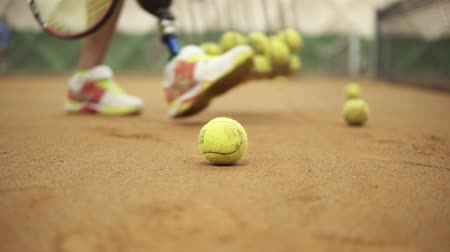 inwalida : Closeup footage of female legs in sports sneakers and prosthesis on her leg picking up tennis balls from the tennis court ground