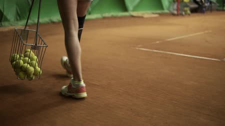 inwalida : Aiming footage of a disabled womans legs. Slender girl collects balls with a tennis basket. Indoors tennis court Wideo
