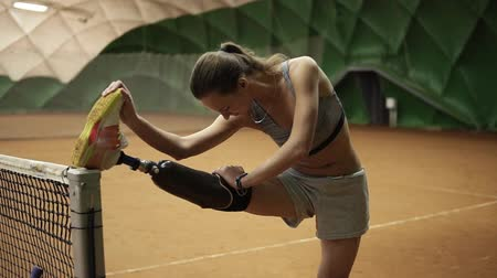 sportolók : A slender disabled girl stretches her injured leg on the tennis net before the game. Prosthesis. Indoors Stock mozgókép
