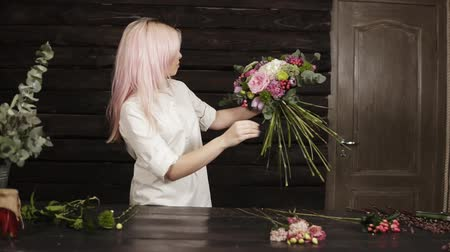 variedade : Professional florist in white shirt decorates a fashionable bouquet complementing with flowers for the perfect composition. Oncoming Stock Footage