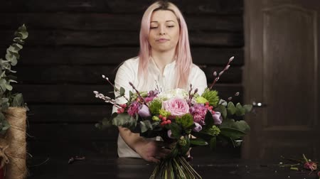 arranging : Charming girl florist presents her work, puts on the table a beautiful bouquet of colorful flowers on long stable stems. Pretty smiling, gesturing with hands. Front view Stock Footage