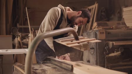 placa de corte : The craftman is working on electric saw machine. Sawing a large wooden bar. Dust and chips are scattering Stock Footage