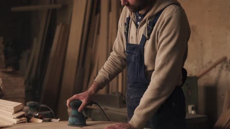 sander : A footage of a carpenter working in overalls. A man grinding a wood in a carpentry shop. Slow motion