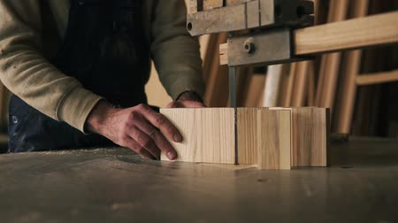 overall : Close up view of a carpenter cutting a wood into pieces. Works with electric saw machine. Wood dust on the surface