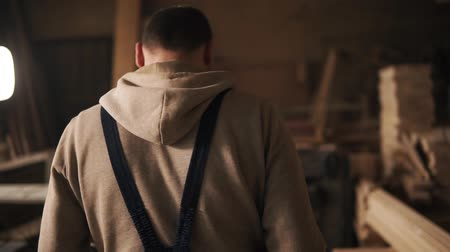 going round : Backside view of a young man in a sweatshirt and blue overalls going through a carpentry workshop. Furniture. Slow motion