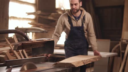 döner : The circular saw in process. The carpenter cuts the edges of a large piece of wood . Carpenters workshop