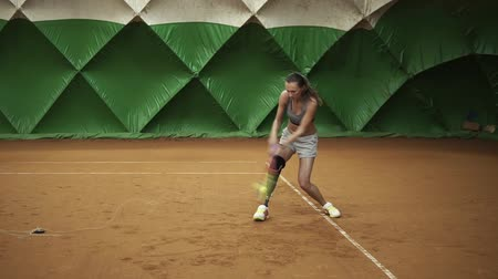 curativo : Backside view of energetic young woman with a prosthesis down her knee is focused on beating the ball on an elastic band. Indoors