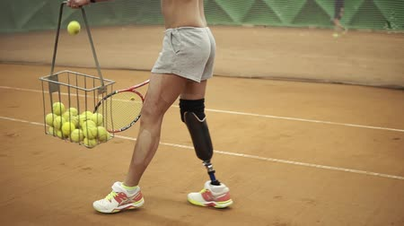 ortopedia : Close up footage of a young disabled girl picking up balls from a tennis court and with racket in her hand. Short shorts, basket for tennis balls. Indoors