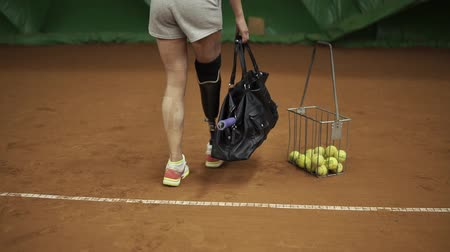 handikap : Smiling girl athlete comes to tennis training, pulls out a racket and goes to the court. Leg prosthesis. Slow motion