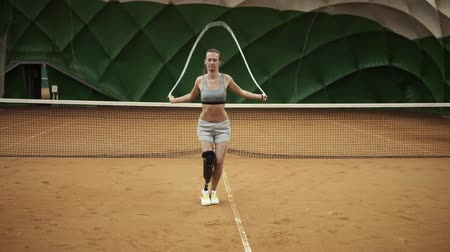 high spirited : A beautiful, brave girl is practicing hard with a skipping rope on a tennis court. On the right foot the prosthesis is up to the knee. Front view