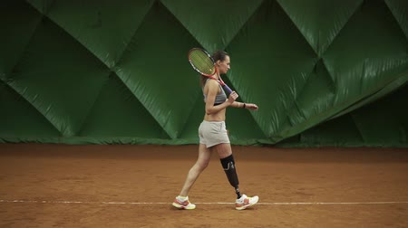 援助 : Disabled young woman is walking through the tennis court with racket. Stands in the stance. Ready for match