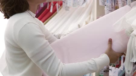 přadeno : Young female shopper searching for fabric in textile shop. Choosing light pink one. Side view Dostupné videozáznamy