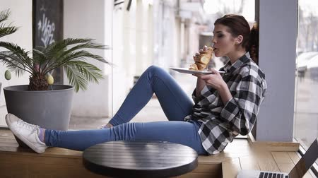 ileri : Side view of a young, pretty girl sitting in a cafe on a wooden seat next to the bright windows. The girl is eating a croissant. She chews and her eyes closed. Enjoy the time