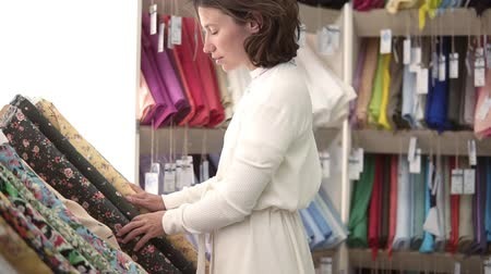 doku : Caucasian woman in white in a tissue shop. Considers the variants of textiles. Unfolds a roll of fabric with a floral print. Coloured textile background Stok Video