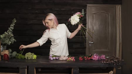 szegfű : Fashionable, smiling girl florist in the process of decoration a bouquet of flowers. Slow motion. Indoors