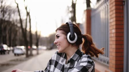 mobile music : Playful, smiling girl in a shirt walking on the street and moving in dance. Funny funky style. Headphones. Expression. Front view Stock Footage