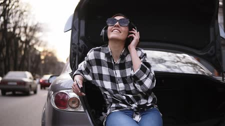 jó hangulatban : Smiling brunette listen to the music in headphone while sitting in the open cars trunk among the road. Cell phone. Good mood