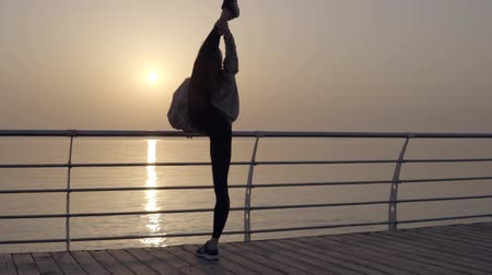 sznurek : Long haired girl stretches her leg with a view of the sea ocean. Dawn Sunrise. Sportswear, leggings, hoodies. Dusk