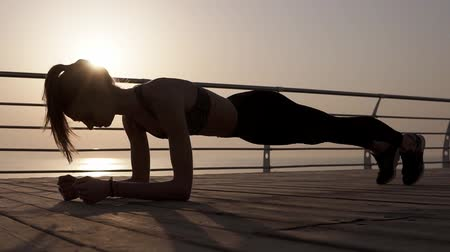 planking : Young female silhouette doing plank exercise on a seaside. Strong body. Dusk. Morning sunrise