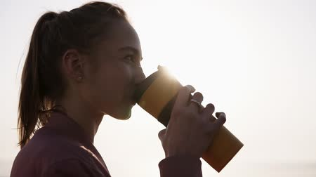 an : Close up of a beautiful, dreaming young woman. Girl is enjoying the moment. Drinks from a sports mug. Breathing. Sun is shining on the background