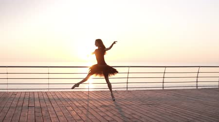 tüt : Ballerina in black ballet tutu and point on embankment above ocean or sea at sunrise. Jumping ballerina, practicing classic exercises. Slow motion