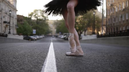 ayak parmakları : Elegant young ballet dancer on the street on an empty road. Stepping on tip toes in pointe. Close up of a ballerinas legs. Slow motion Stok Video