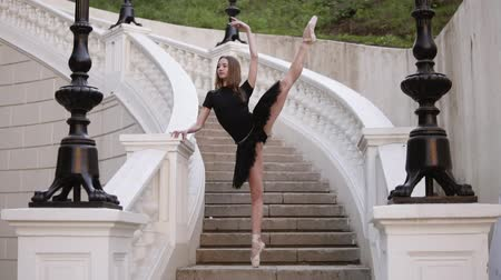 tüt : Front view of a graceful ballet movements. Young, blonde haired ballerina doing vertical twine and posing standing on a beginning of street stairs in black tutu. Daytime. Slow motion Stok Video