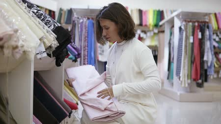 szál : Gorgeous young woman in textile shop with a variety of tissues on the background. The customer decides what type of cloth to choose. Considering different types. Take blue one roll. Side view Stock mozgókép